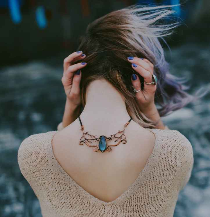woman wears gold colored blue gemstone pendant necklace