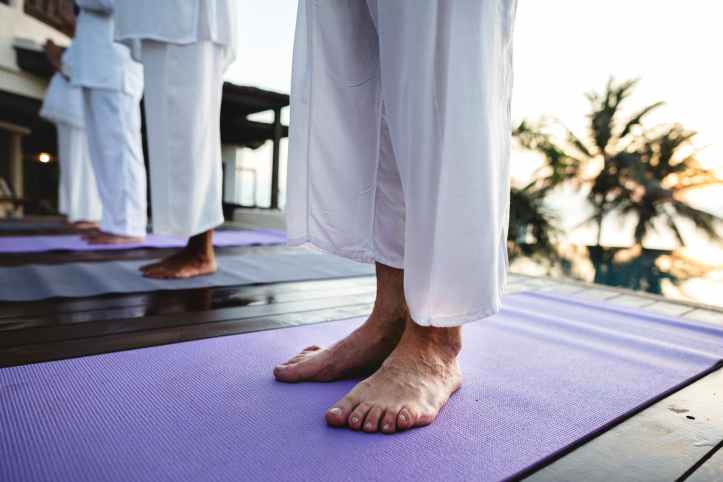photo of people standing on purple yoga mats