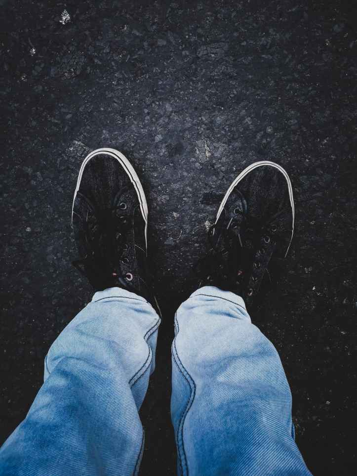person in pair of black low top sneakers