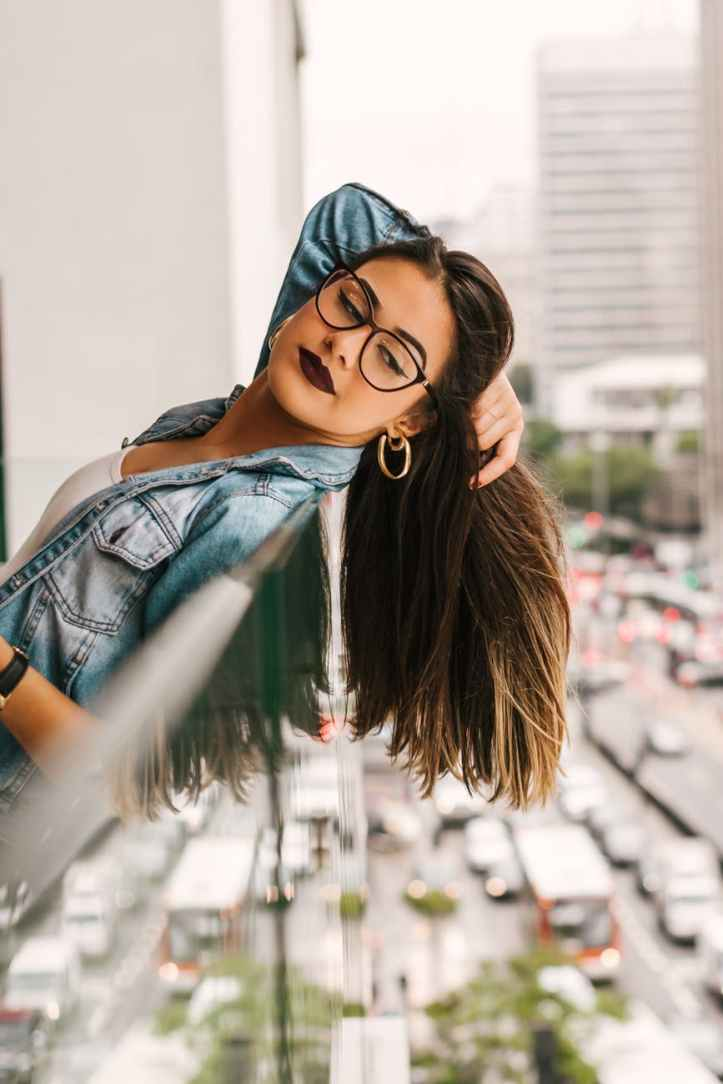 photo of woman leaning backwards on glass railing while holding her hair and looking down