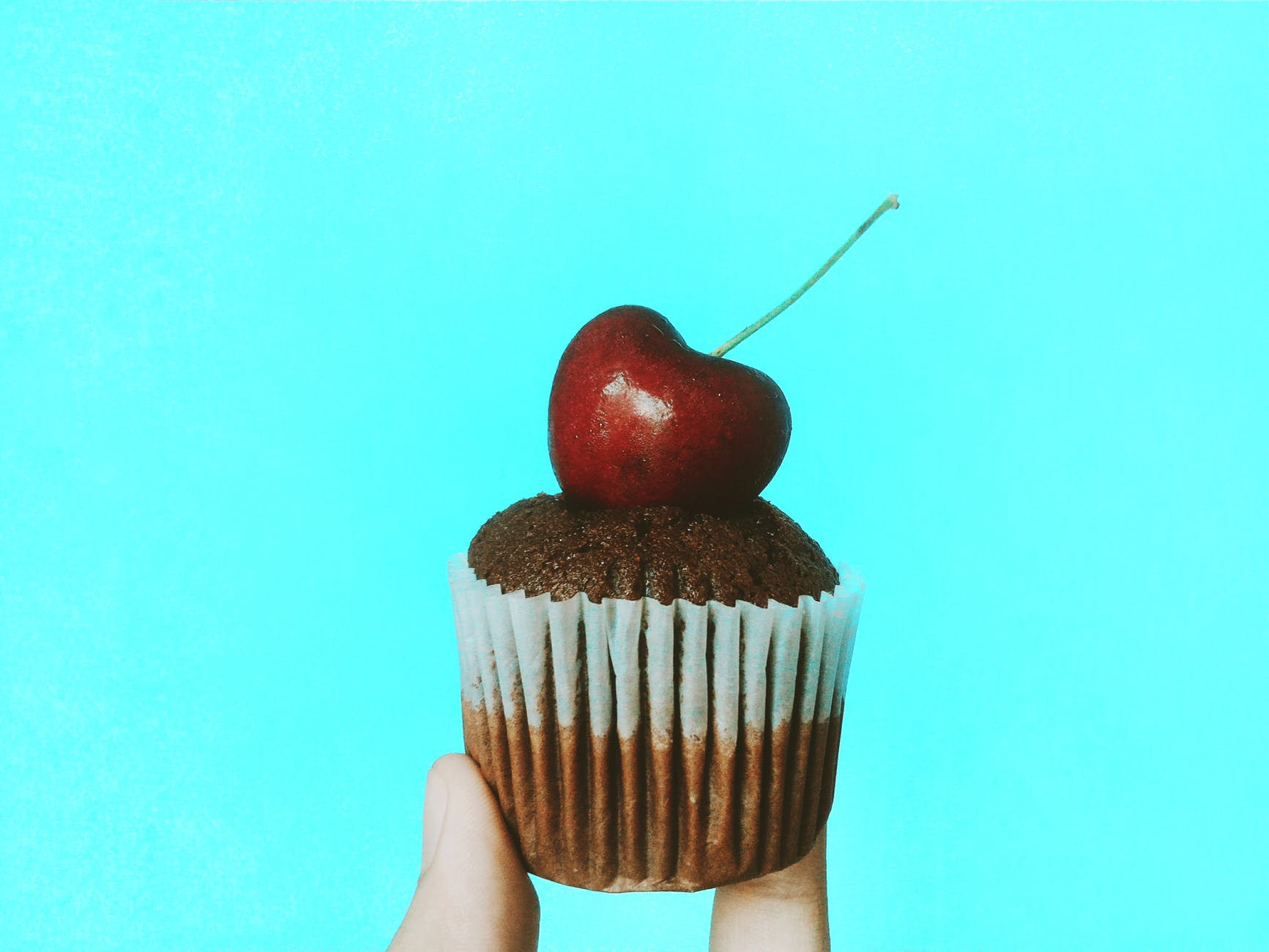 person holding chocolate cupcake with cherry topping