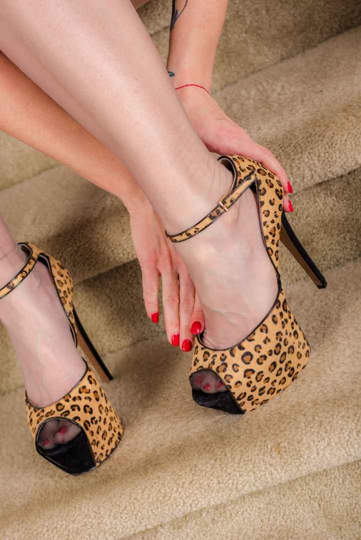 woman wearing brown and black leopard print platform ankle strap stilettos