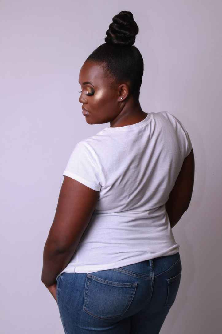 back view photo of woman in white t shirt and blue jeans posing in front of white background