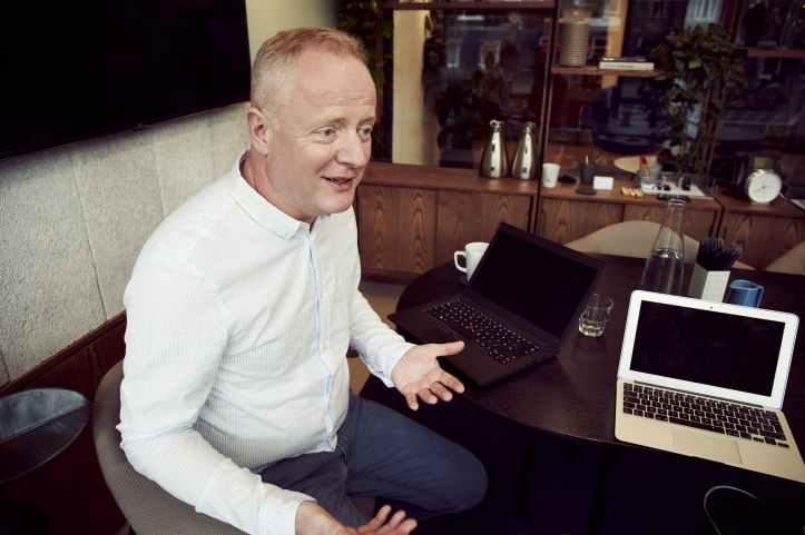 man wearing long sleeved shirt sitting beside table