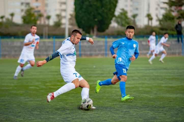 man wearing blue shirt looking on ball
