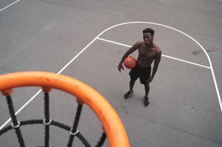 man standing near basketball hoop holding a basketbal