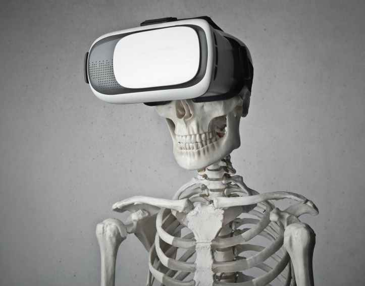 portrait photo of skeleton in front of gray background with white and black vr goggles on