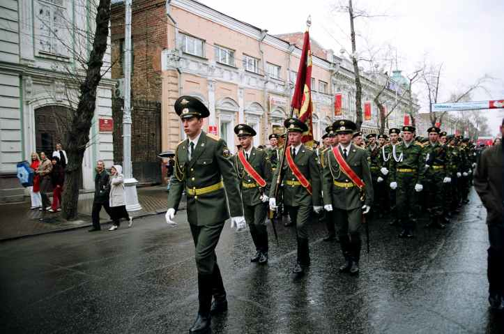 military personnel parades on road