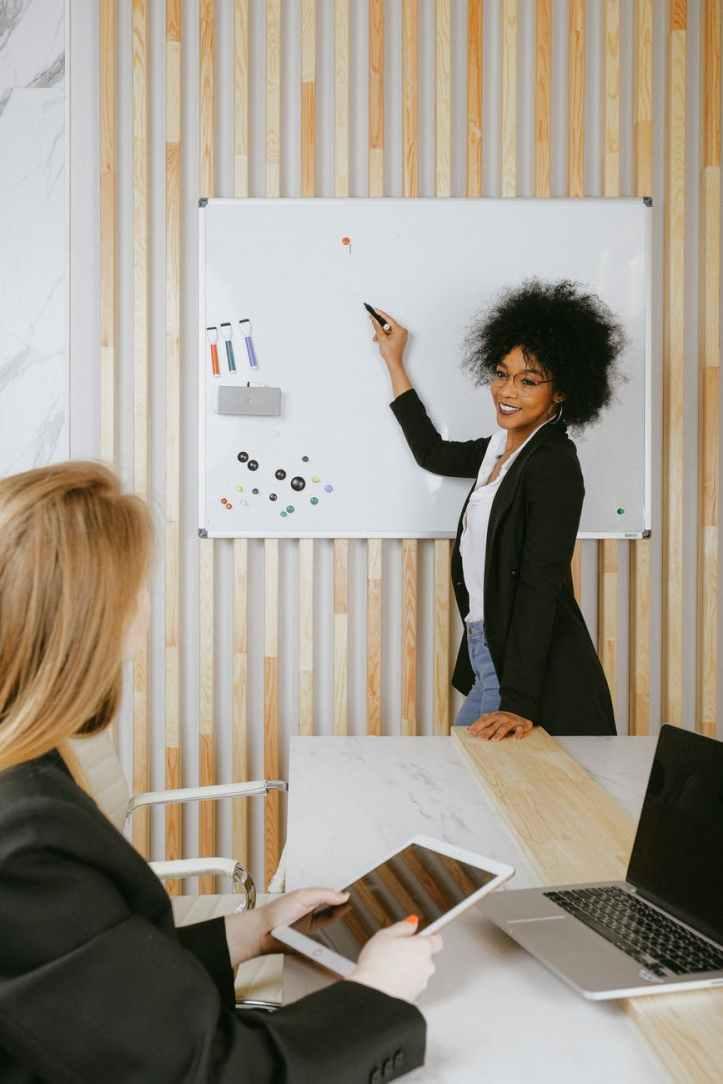 femme pointant sur tableau blanc