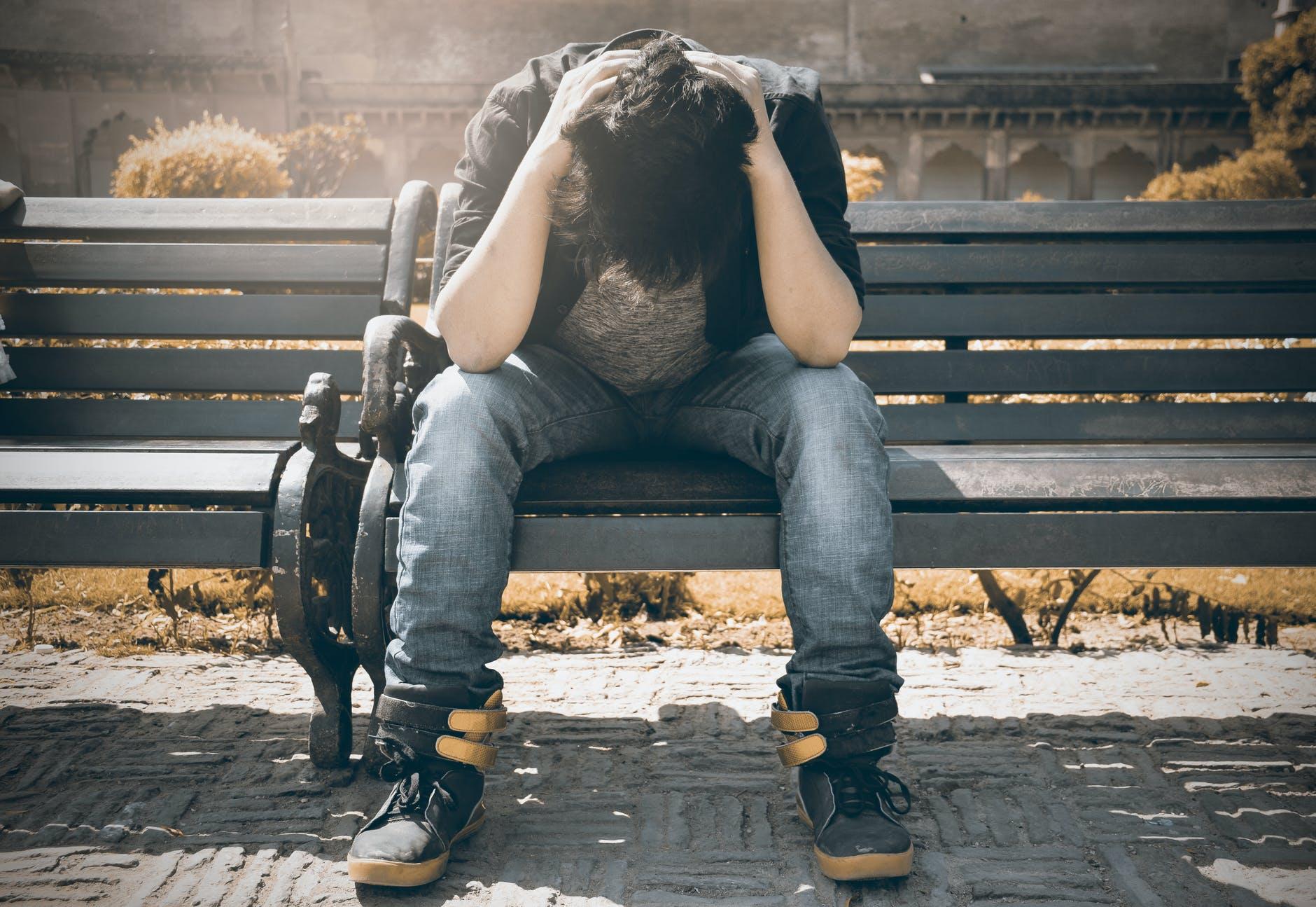 homme en chemise noire et pantalon en denim gris assis sur un banc rembourre gris