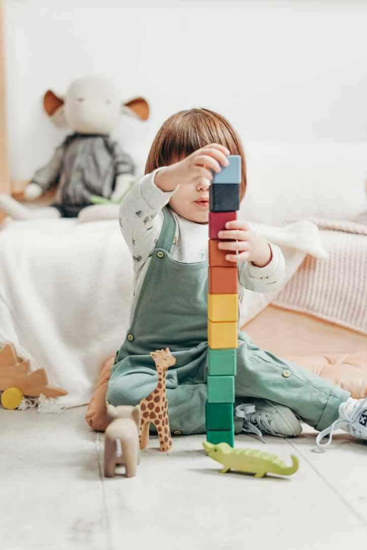 enfant en haut a manches longues blanc et pantalon salopette jouant avec des blocs lego