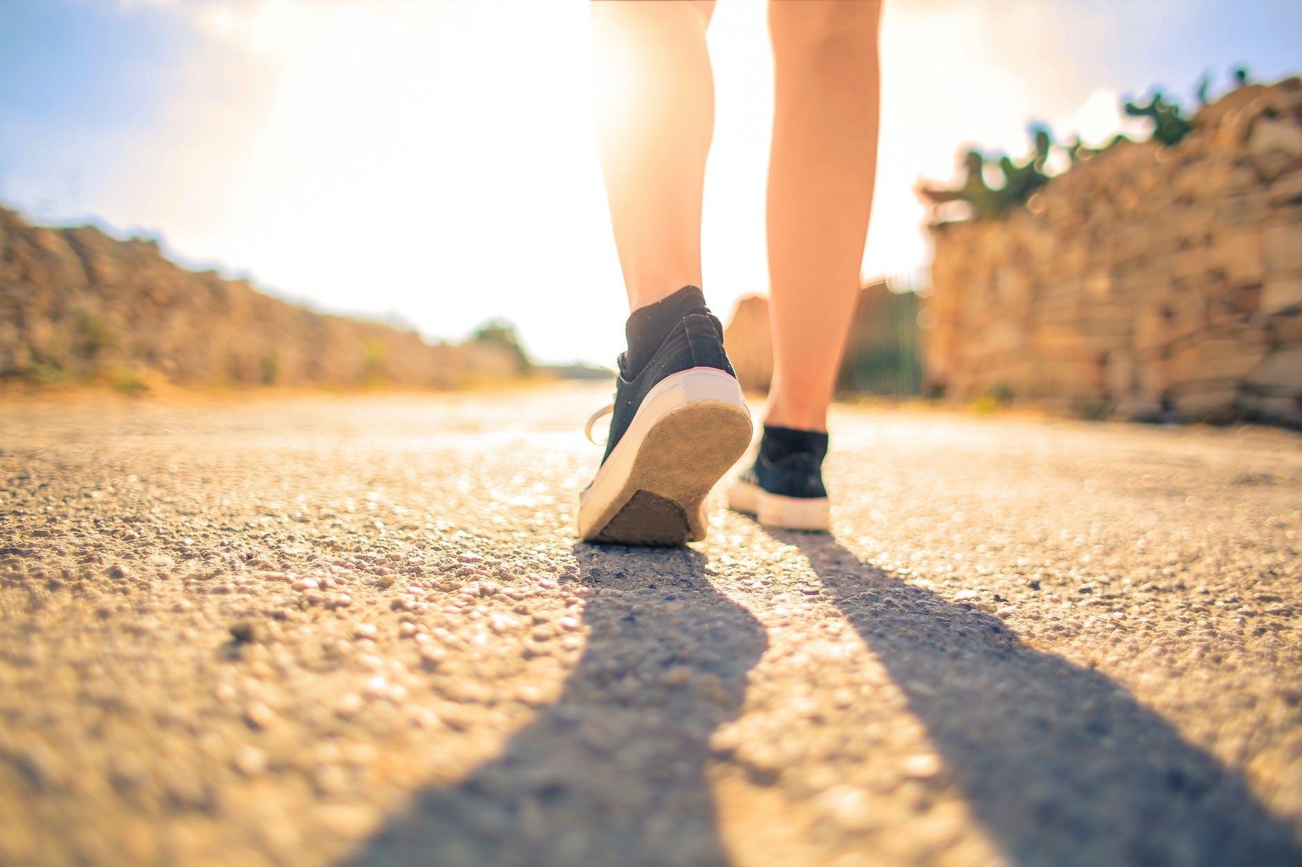 femme marchant sur le chemin sous le soleil
