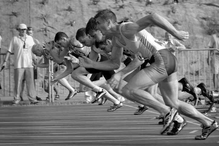 athletes qui courent sur un ovale d athletisme en photographie en niveaux de gris
