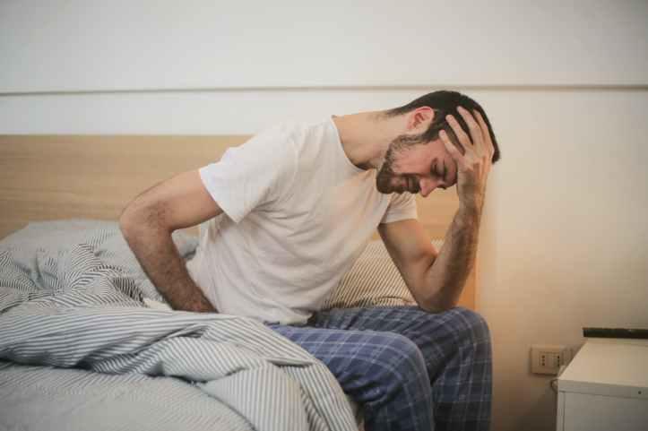 jeune homme en vetements de nuit souffrant de maux de tete le matin