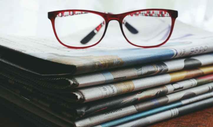 lunettes encadrees rouges sur les journaux